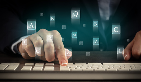 Business woman typing on keyboard with letters around Stock Photo