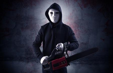 Assassin grossier armé dans un concept de pièce sanglante vide avec une clé à maillet pour tronçonneuse