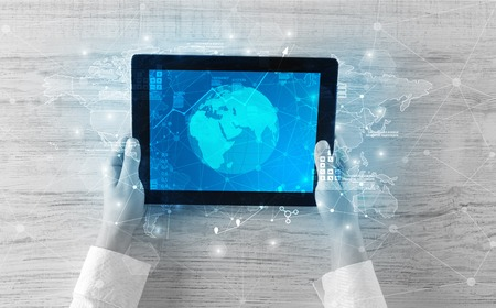 Hand touching tablet with worldwide reports links and statistics concept Stock Photo