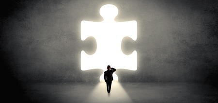 Businessman  standing and looking to a big puzzle piece Imagens
