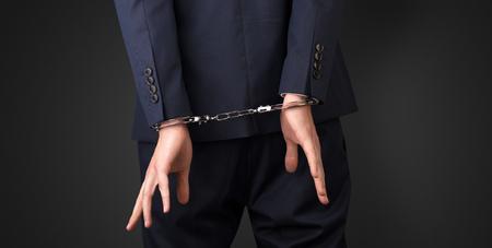 Cerrar ahora la mano de los hombres arrestados con fondo oscuro y esposas
