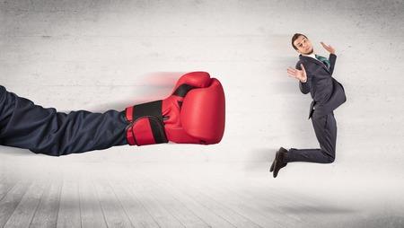Brazo con guantes de boxeo rojos golpea el concepto de trabajador de oficina