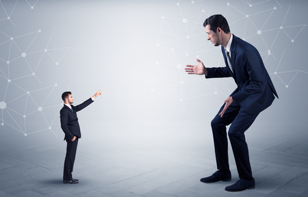 Small businessman aiming at a big businessman with connection and network concept Фото со стока