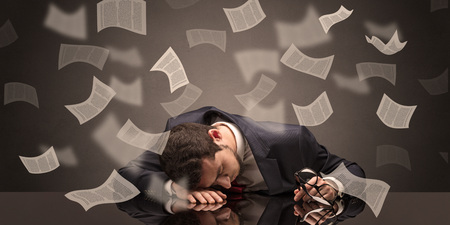 Young businessman fell asleep at the table with paperwork concept