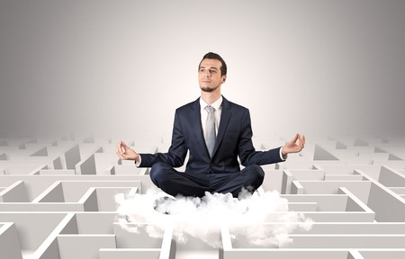 Young businessman meditate in yoga position on a cloud with infinity maze concept Banco de Imagens
