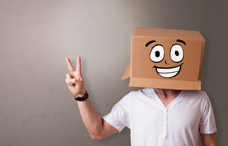 Young boy standing and gesturing with a cardboard box on his head Imagens