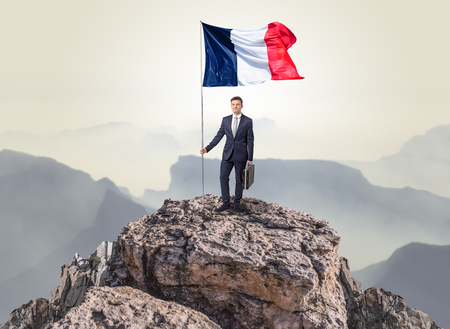 Successful businessman on the top of a mountain holding France victory flag