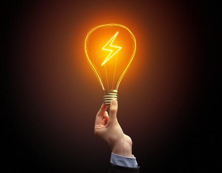 Hand, die Glühbirne auf dunklem Hintergrund hält. Neues Öko-Ideenkonzept Standard-Bild
