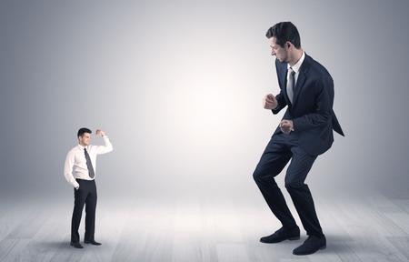 Grand jeune homme d'affaires débutant effrayé par un petit homme d'affaires fort