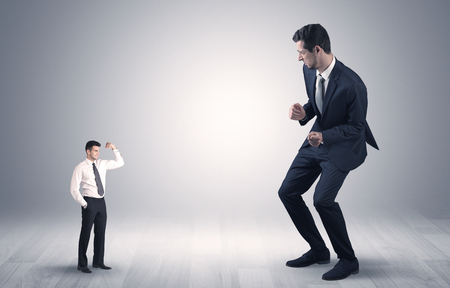 Grote debuterende jonge zakenman bang voor kleine sterke zakenman