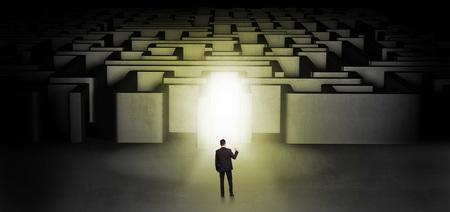 Lost businessman standing at the dark labyrinth with illuminated door Reklamní fotografie
