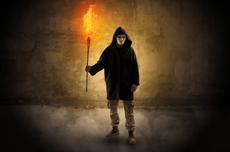 Ugly wayfarer with burning torch in his hand in front of a crumbly wall concept Imagens