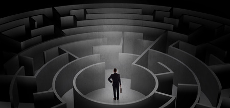 Businessman can not decide which entrance to chose in a middle of a dark maze 版權商用圖片