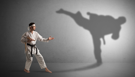Young karate man confronting with his own shadow Stock Photo
