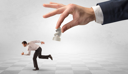 Small frail businessman with suitcase running away from big hand with chessman concept Banque d'images - 121851443