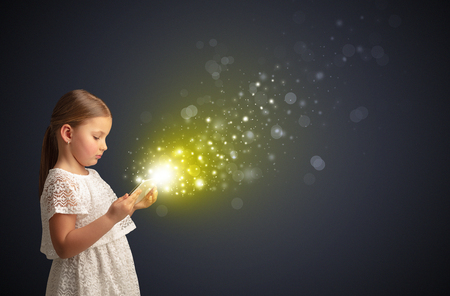 Little cute girl playing on sparkling tablet Stockfoto