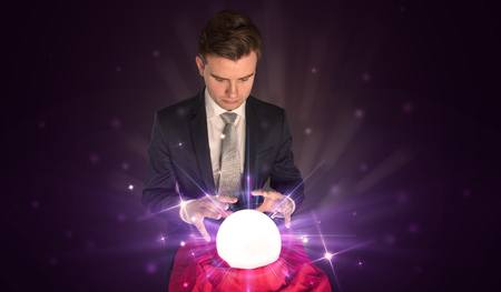 Young businessman sitting with crystal ball in action 免版税图像
