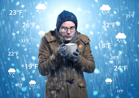 Young man freezing in warm clothing with weather condition and forecast concept Stok Fotoğraf