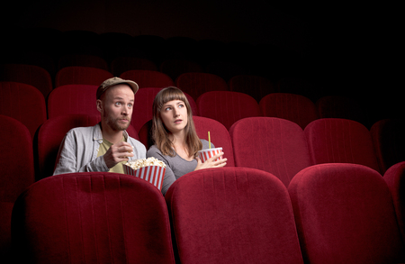 Young cute couple sitting alone at red movie theatre and having fun Stockfoto