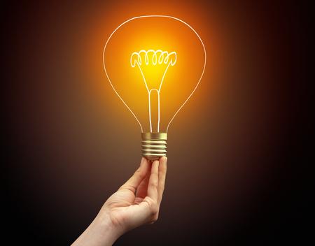Hand holding light bulb on dark background, new idea concept
