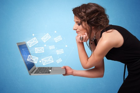 Woman holding laptop with online services symbols Imagens