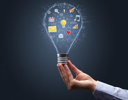 Hand holding light bulb on dark background. New apps concept Banco de Imagens