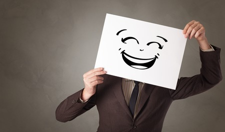Casual person holding a paper in front of his face with drawn emoticon face Archivio Fotografico