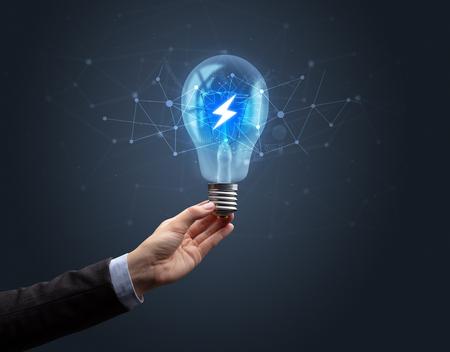 Hand holding light bulb on dark background. Networking idea concept Banco de Imagens