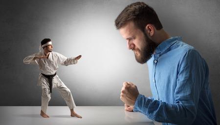 Hombre inconformista gigante gritando a un pequeño hombre de karate Foto de archivo