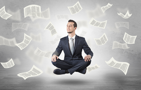 Young businessman meditating with documents and papers flying around him
