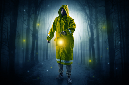 Man in raincoat coming from dark forest with glowing lantern in his hand concept Stock Photo