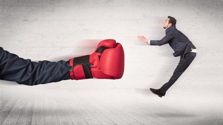 Arm with red boxing gloves hits office worker concept