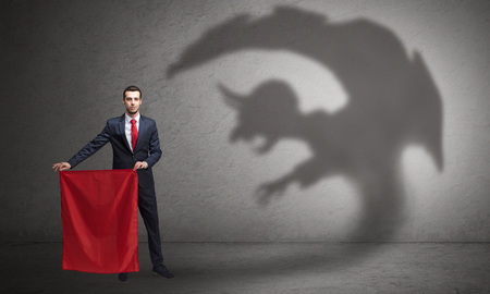 Businessman standing with red cloth in his hand and imp shadow on the background