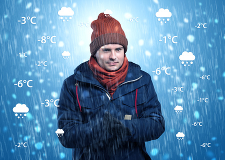 Young man freezing in warm clothing with weather condition and forecast concept Standard-Bild