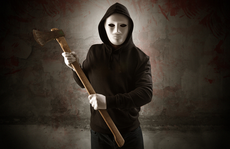 Assassino maleducato armato in un concetto di stanza vuota insanguinata con chiave a martello per motosega ascia pistola Archivio Fotografico
