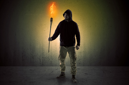Ugly scary man with burning flambeau walking in an empty space