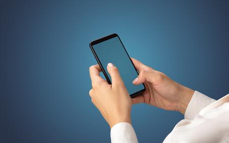 Mockup for female hand using frameless smartphone with dark background Reklamní fotografie