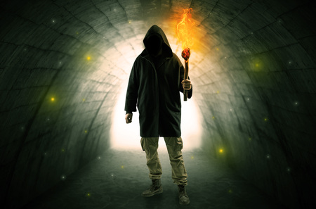 Ugly man with burning flambeau walking in a dark tunnel