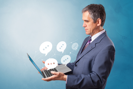 Man holding laptop with a few speech bubble symbols
