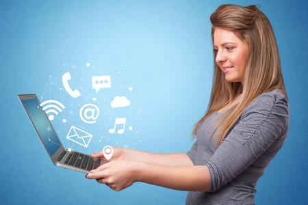 Woman holding laptop with online services symbols Banco de Imagens