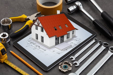 Tablet with construction tools and 3d home plan concept 版權商用圖片