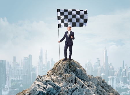 Successful businessman on the top of a city holding goal flag Standard-Bild