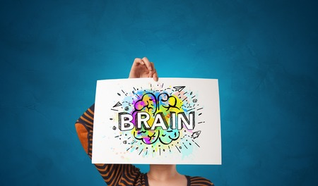 Young person holding white paper in front of her head with colorful brain concept