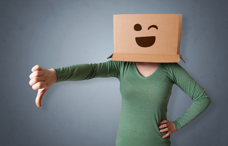 Funny woman wearing cardboard box on her head with smiley face Imagens