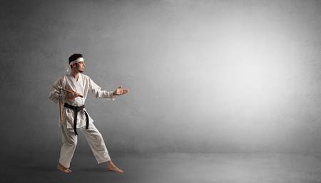 Kleiner Karate-Mann, der in einem leeren grauen Kopienraum kämpft