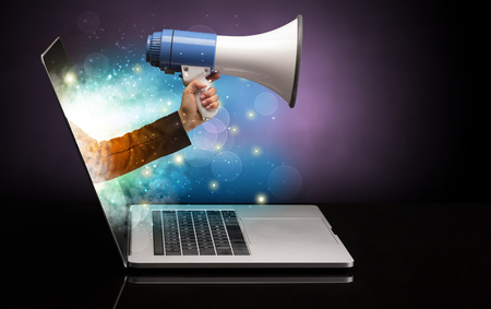 Hand with loudspeaker coming out of a laptop with sparkling effects