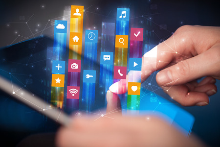 Businessman hand using tablet with flying application icons around Reklamní fotografie