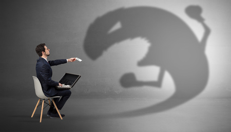 Young businessman staying and  negotiate with a monster shadow Stock Photo - 122923699