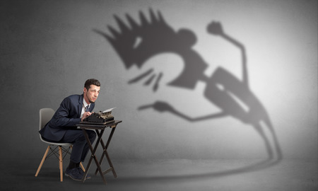 Man working hard and he is afraid of a yelling shadow Banco de Imagens