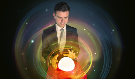 Young handsome man looking to the future of the universe in a crystal ball Stock Photo